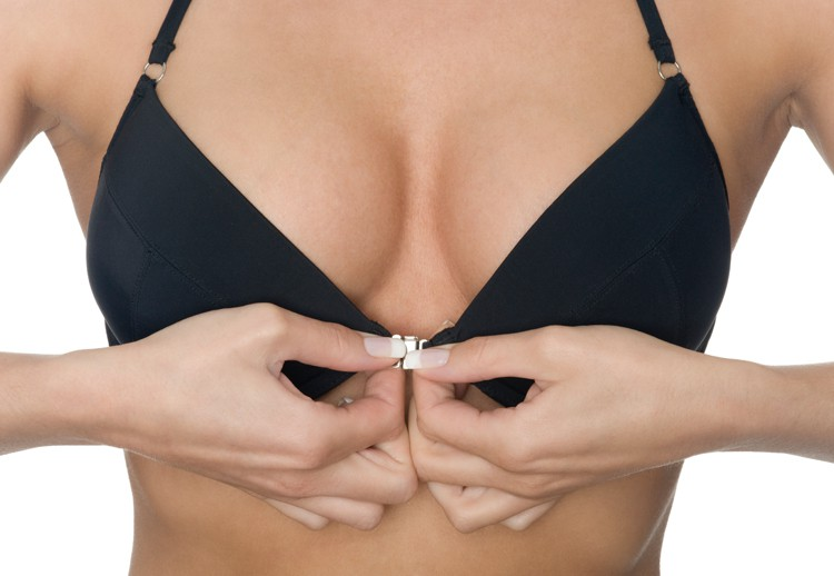Image of a woman fastening her bra from the front